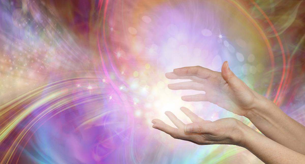 Sending you beautiful healing energy vibes – female cupped hands with white energy formation flowing outwards, sparkles and colours moving in all directions with copy space