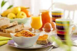 Frühstück mit Brot, Obst, Cornflakes, Eiern und Saft