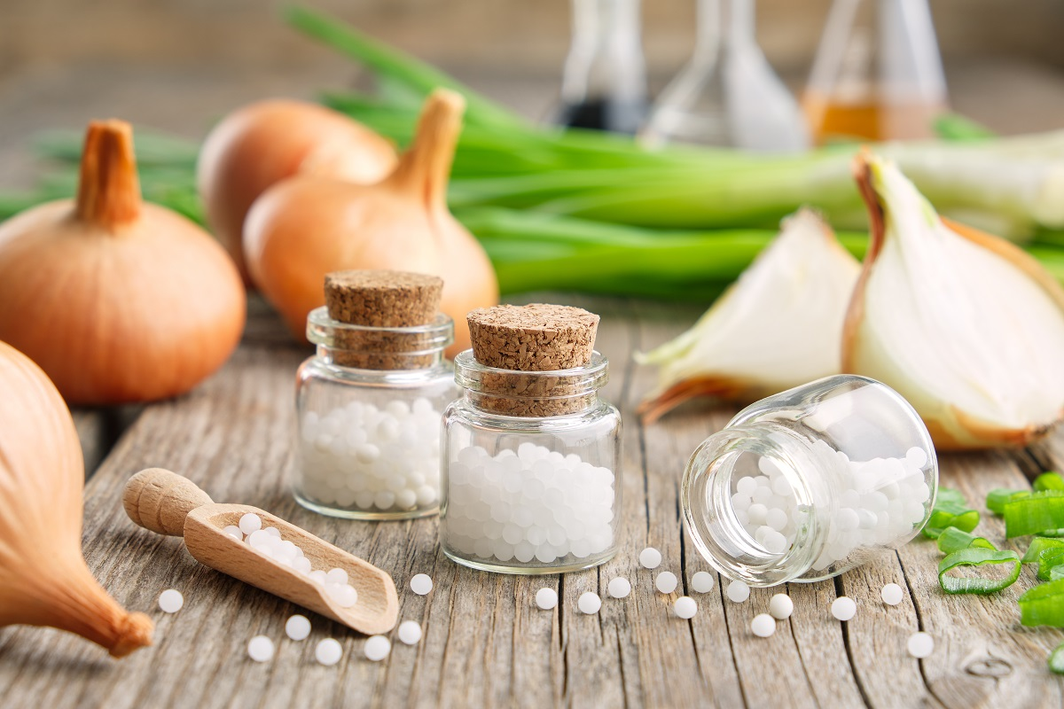 Bottles of homeopathic globules, onion bulbs and fresh green onions. Allium cepa homeopathic remedies.